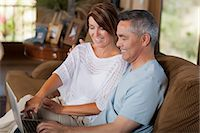 Couple using laptop together on sofa Stock Photo - Premium Royalty-Freenull, Code: 614-06718946
