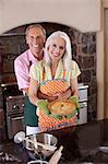 Older couple holding pie in kitchen Stock Photo - Premium Royalty-Free, Artist: Blend Images, Code: 614-06719068
