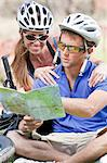 Couple reading map on mountain bikes Stock Photo - Premium Royalty-Free, Artist: Blend Images, Code: 614-06719135