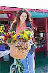 Woman carrying flowers in bicycle basket Stock Photo - Premium Royalty-Free, Artist: Minden Pictures, Code: 614-06719215