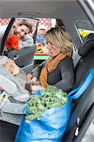 Woman buckling son in car seat Stock Photo - Premium Royalty-Freenull, Code: 614-06719261