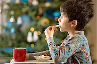 Boy eating Christmas cookies Stock Photo - Premium Royalty-Freenull, Code: 614-06719317
