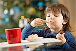 Girl eating Christmas cookies Stock Photo - Premium Royalty-Free, Artist: Raymond Forbes, Code: 614-06719320