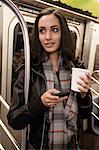 Woman using cell phone on subway Stock Photo - Premium Royalty-Free, Artist: Blend Images, Code: 614-06719725