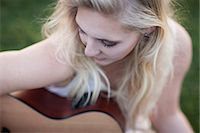 Woman playing guitar in grass Stock Photo - Premium Royalty-Freenull, Code: 614-06719773