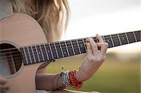 Woman playing guitar in grass Stock Photo - Premium Royalty-Freenull, Code: 614-06719789