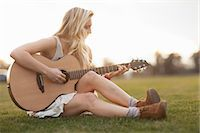 Woman playing guitar in grass Stock Photo - Premium Royalty-Freenull, Code: 614-06719794