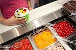Girl putting toppings on frozen yogurt Stock Photo - Premium Royalty-Free, Artist: Anna Huber, Code: 614-06719836