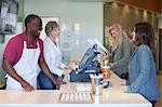 Cashiers talking to customers in store Stock Photo - Premium Royalty-Free, Artist: Blend Images, Code: 614-06719845