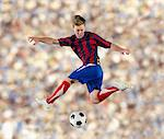 Soccer player kicking ball in air Stock Photo - Premium Royalty-Free, Artist: Cultura RM, Code: 614-06719873