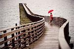 Woman with umbrella on wooden pier Stock Photo - Premium Royalty-Free, Artist: Russell Monk, Code: 614-06719876