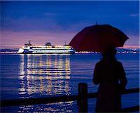 Woman with umbrella admiring cruise ship Stock Photo - Premium Royalty-Freenull, Code: 614-06719879
