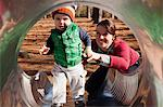 Mother helping son play on slide Stock Photo - Premium Royalty-Free, Artist: Blend Images, Code: 614-06720004