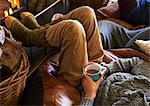 Boy drinking cup of coffee by fire Stock Photo - Premium Royalty-Free, Artist: CulturaRM, Code: 6113-06720283