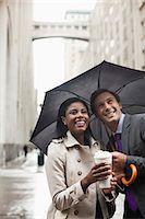 Business people holding umbrella on city street Stock Photo - Premium Royalty-Freenull, Code: 6113-06720512