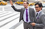 Businessmen hailing taxi on city street Stock Photo - Premium Royalty-Free, Artist: Robert Harding Images, Code: 6113-06720541