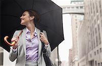 people with umbrellas in the rain - Businesswoman holding umbrella on city street Stock Photo - Premium Royalty-Freenull, Code: 6113-06720546
