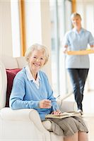 Older woman smiling in armchair Stock Photo - Premium Royalty-Freenull, Code: 6113-06720639