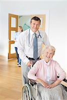 Doctor pushing older patient in wheelchair Stock Photo - Premium Royalty-Freenull, Code: 6113-06720660
