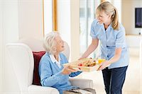 Caregiver giving older woman tray of food Stock Photo - Premium Royalty-Freenull, Code: 6113-06720661