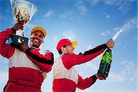 Racers holding trophy and champagne Stock Photo - Premium Royalty-Freenull, Code: 6113-06720779