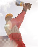 Racer holding trophy at award ceremony Stock Photo - Premium Royalty-Freenull, Code: 6113-06720801