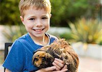 Smiling boy holding guinea pig outdoors Stock Photo - Premium Royalty-Freenull, Code: 6113-06720864