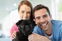 pvg - Smiling couple petting dog indoors Stock Photo