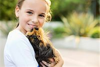 Smiling girl holding guinea pig outdoors Stock Photo - Premium Royalty-Freenull, Code: 6113-06720916