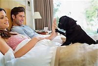 pvg - Woman teaching dog 'high five' in bed Stock Photo - Premium Royalty-Freenull, Code: 6113-06720964