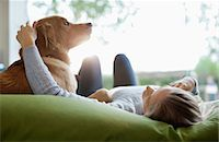 Woman petting dog on bed Stock Photo - Premium Royalty-Freenull, Code: 6113-06720973