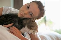 Girl petting cat on bed Stock Photo - Premium Royalty-Freenull, Code: 6113-06720984