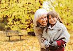 Older woman and granddaughter smiling in park