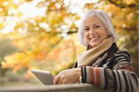 people sitting on bench - Older woman using tablet computer outdoors Stock Photo - Premium Royalty-Freenull, Code: 6113-06721171