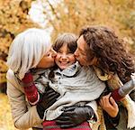 Woman and daughter kissing girl in park