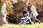 Couple pushing baby in stroller in park Stock Photo - Premium Royalty-Freenull, Code: 6113-06721258