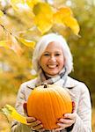 Older woman holding pumpkin in park Stock Photo - Premium Royalty-Free, Artist: Cultura RM, Code: 6113-06721291