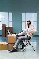 piles of work - Businessman using a laptop in a warehouse with cardboard boxes Stock Photo - Premium Royalty-Freenull, Code: 630-06722225