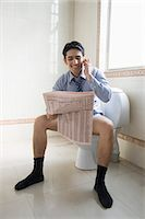 Businessman talking on a mobile phone and reading a newspaper on a toilet seat Stock Photo - Premium Royalty-Freenull, Code: 630-06722230