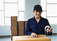 east indian (male) - Delivery man packing cardboard box and smiling Stock Photo - Premium Royalty-Freenull, Code: 630-06722238