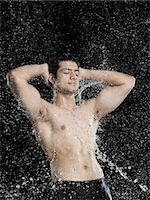 Bare chested man splashed with water Stock Photo - Premium Royalty-Freenull, Code: 630-06722702