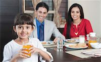 Portrait of a girl holding a glass of juice with her parents in the background Stock Photo - Premium Royalty-Freenull, Code: 630-06723023