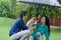 people with umbrellas in the rain - Family enjoying in rain in a park Stock Photo - Premium Royalty-Freenull, Code: 630-06723060