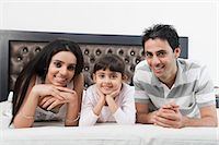 Portrait of a couple lying on the bed with their daughter Stock Photo - Premium Royalty-Freenull, Code: 630-06723079