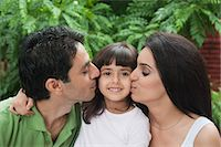 Parents kissing their daughter Stock Photo - Premium Royalty-Freenull, Code: 630-06723112