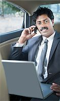 South Indian businessman using a laptop and talking on a mobile phone in the car Stock Photo - Premium Royalty-Freenull, Code: 630-06724907