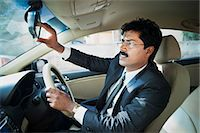South Indian businessman adjusting the rear view mirror of a car Stock Photo - Premium Royalty-Freenull, Code: 630-06724908