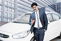 South Indian businessman text messaging on a mobile phone in front of a car Stock Photo - Premium Royalty-Freenull, Code: 630-06724913