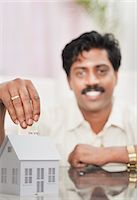 South Indian man putting money in a model home Stock Photo - Premium Royalty-Freenull, Code: 630-06724930