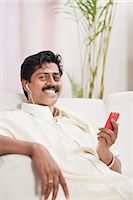 South Indian man listening to a mp3 player Stock Photo - Premium Royalty-Freenull, Code: 630-06724934